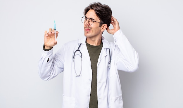 幸せに笑って、空想にふけるか、疑う若いヒスパニック系の男性。ドクターシリンジのコンセプト