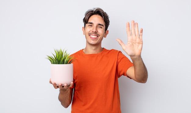 Молодой латиноамериканец счастливо улыбается, машет рукой, приветствует и приветствует вас. концепция декоративного растения