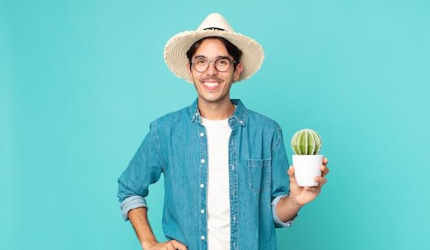 腰に手を当てて幸せそうに笑って自信を持ってサボテンを持っている若いヒスパニック系男性