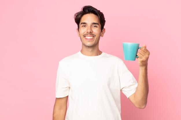 腰に手を当てて幸せそうに笑って自信を持ってコーヒーマグカップを持っている若いヒスパニック系男性