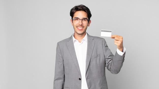 젊은 히스패닉 남자는 엉덩이에 손을 대고 행복하게 웃고 신용 카드를 들고 자신감을 가지고 있습니다.