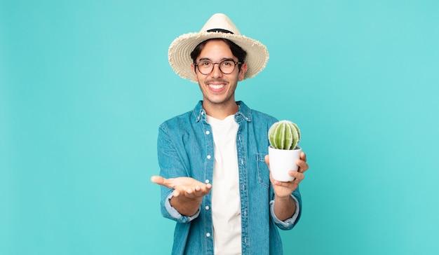 フレンドリーで幸せに笑って、コンセプトを提供し、サボテンを保持している若いヒスパニック系男性