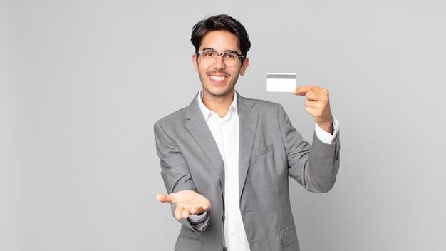 젊은 히스패닉 남자는 친절하게 웃으며 개념을 보여주고 신용 카드를 들고 행복하게 웃고 있습니다.