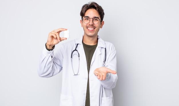 若いヒスパニック系の男性は、フレンドリーで幸せに笑って、コンセプトを提供し、示しています。薬瓶の概念を持つ医師