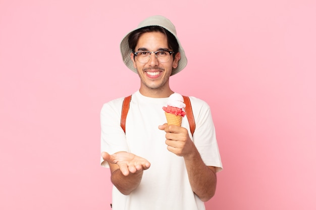 Young hispanic man smiling happily with friendly and  offering and showing a concept and holding an ice cream