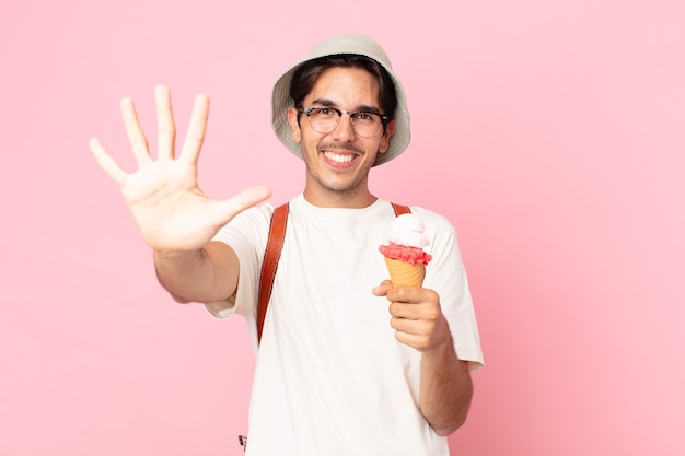 Young hispanic man smiling and looking friendly, showing number five and holding an ice cream