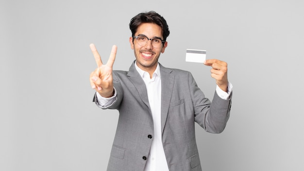 Young hispanic man smiling and looking happy, gesturing victory or peace and holding a credit card