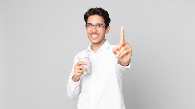 誇らしげにそして自信を持って笑顔でナンバーワンを作り、テイクアウトコーヒーを持っている若いヒスパニック系男性