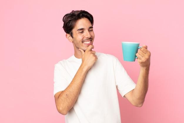 あごに手で幸せで自信に満ちた表情で笑って、コーヒーのマグカップを持っている若いヒスパニック系の男性