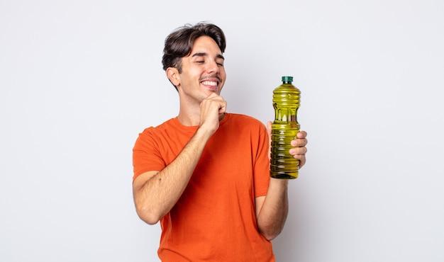 ヒスパニック系の若い男性は、あごに手を添えて幸せで自信に満ちた表情で笑っています。オリーブオイルの概念