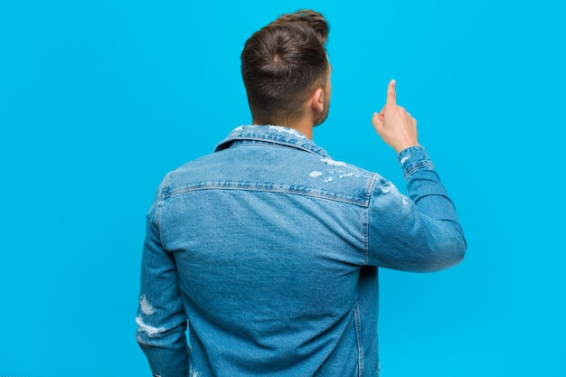 Young hispanic man standing and pointing to object on copy space, rear view against blue wall