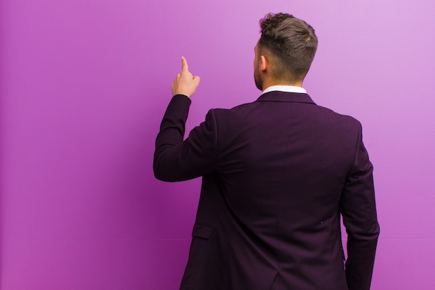 Young hispanic man standing and pointing to object on copy space, rear view