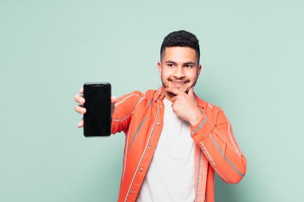 表現を考え、携帯電話を持っている若いヒスパニック系男性