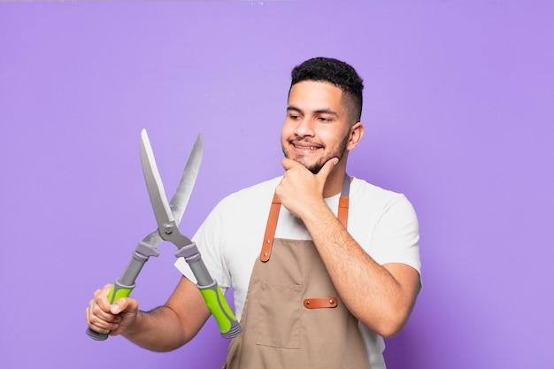 表現を考えている若いヒスパニック系の男性。農夫または庭師の概念