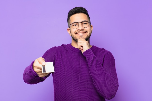 Young hispanic man thinking expression and holding a credit card