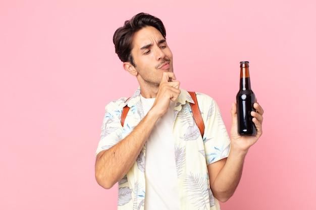 Молодой латиноамериканец думает, сомневается и смущается и держит бутылку пива