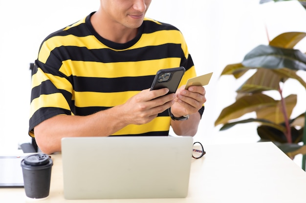 Young hispanic man using credit card to payment online with smartphone and laptop computer at home or creative workplace office.