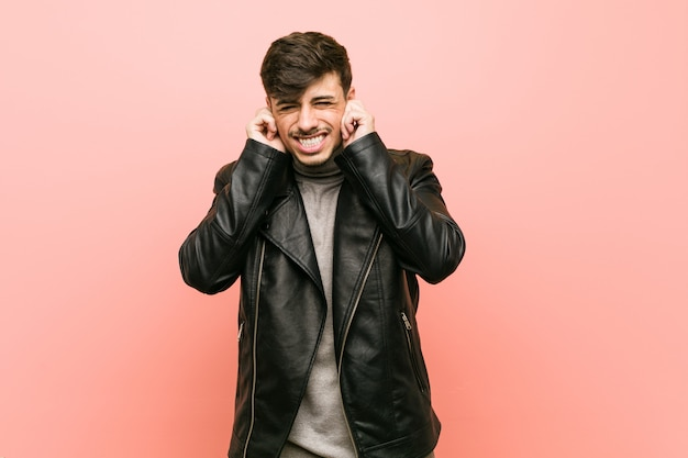 Young hispanic man wearing a leather jacket covering ears with hands.