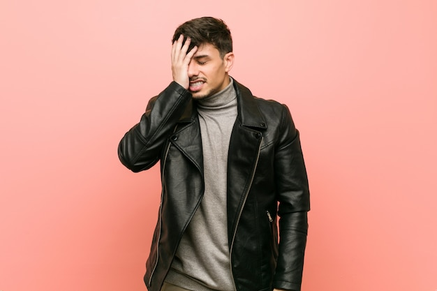 Young hispanic man wearing a leather jacket forgetting something, slapping forehead with palm and closing eyes.