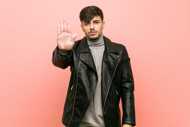 Young hispanic man wearing a leather jacket standing with outstretched hand showing stop sign, preventing you.