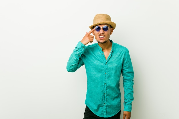 Young hispanic man wearing a summer clothes showing a disappointment gesture with forefinger.