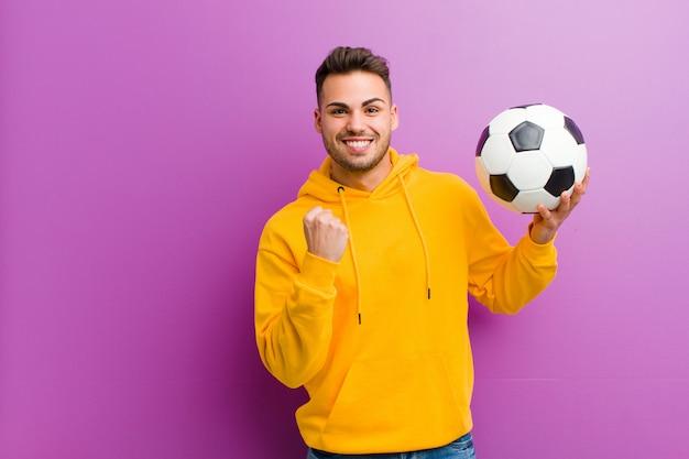 紫色の背景に対してサッカーボールを持つ若いヒスパニック男