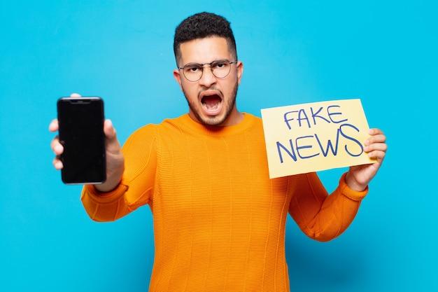 怒っている表情の偽のニュースの概念を持つ若いヒスパニック系男性