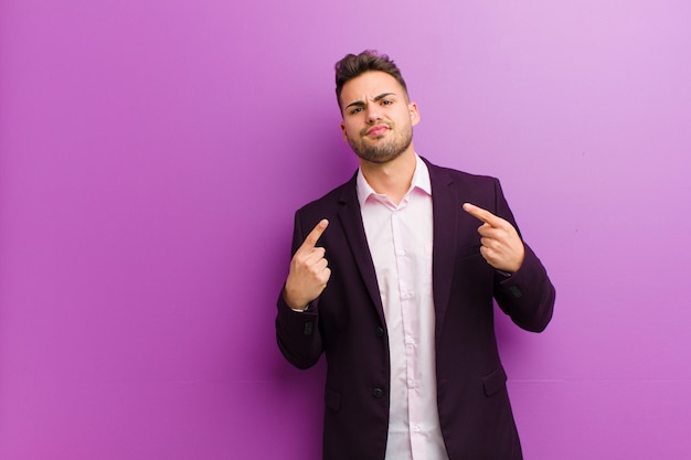 Young hispanic man with a bad attitude looking proud and aggressive, pointing upwards or making fun sign with hands