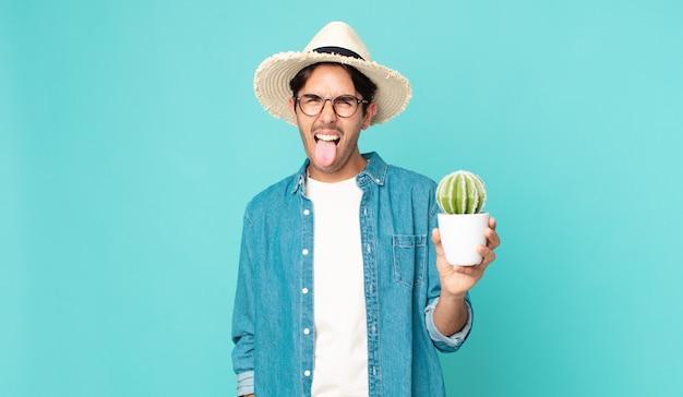 陽気で反抗的な態度、冗談を言って舌を突き出し、サボテンを持っている若いヒスパニック系男性