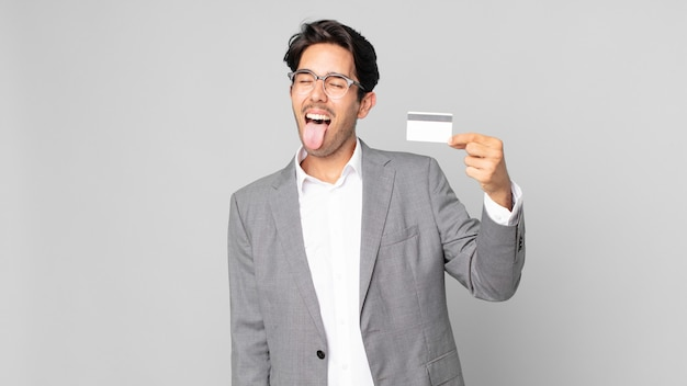 Young hispanic man with cheerful and rebellious attitude, joking and sticking tongue out and holding a credit card