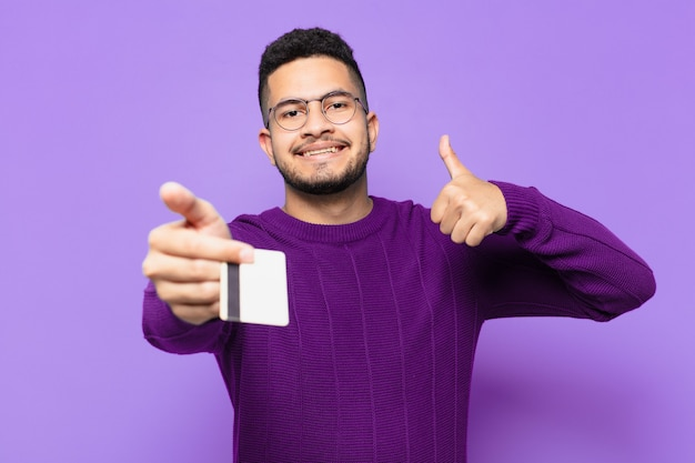 Young hispanic man with happy expression and holding a credit card