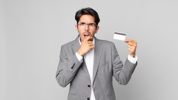 입과 눈을 크게 뜨고 턱에 손을 대고 신용 카드를 들고 있는 젊은 히스패닉 남자