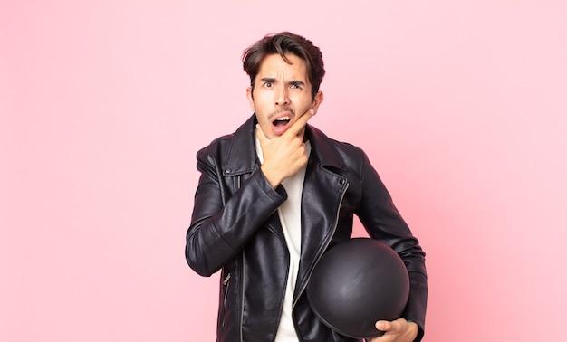 口と目を大きく開いて、あごに手を持っている若いヒスパニック系の男性。バイクライダーのコンセプト