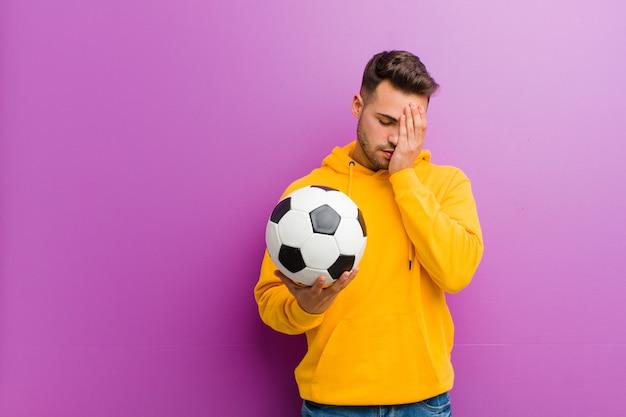 Young hispanic man with a soccer ball  purple