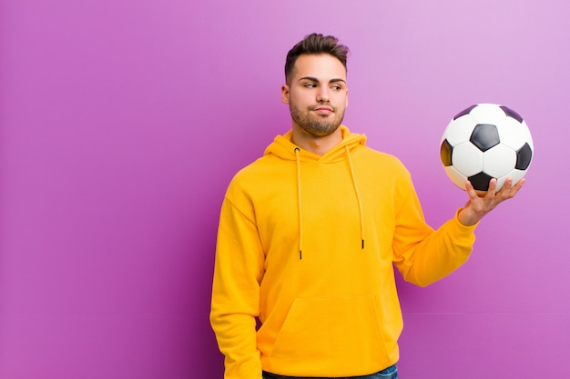 Young hispanic man with a soccer ball