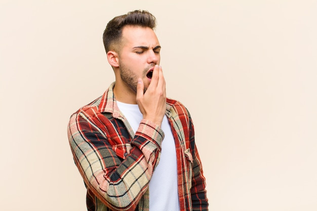 Young hispanic man yawning lazily early in the morning, waking and looking sleepy, tired and bored against isolated wall