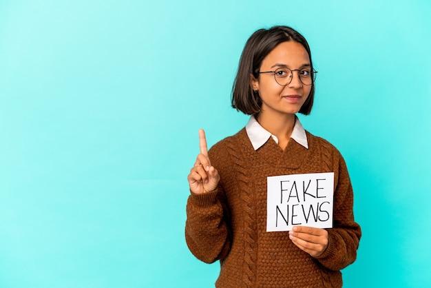 指でナンバーワンを示す偽のニュースプラカードを保持している若いヒスパニック混血の女性。