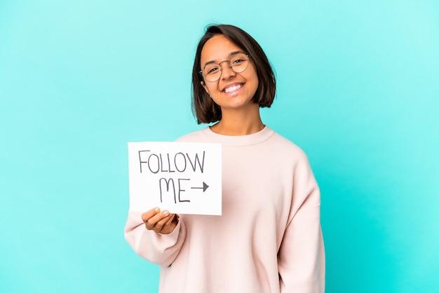 Молодая латиноамериканская женщина смешанной расы, держащая плакат «следуй за мной», счастлива, улыбается и весела.