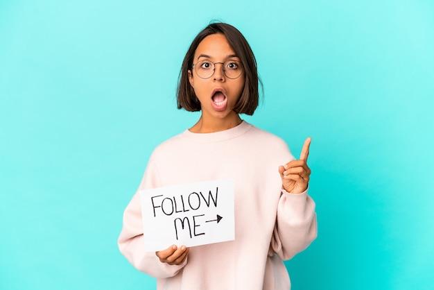 Молодая латиноамериканская женщина смешанной расы, держащая плакат «следовать за мной» с идеей, концепцией вдохновения.