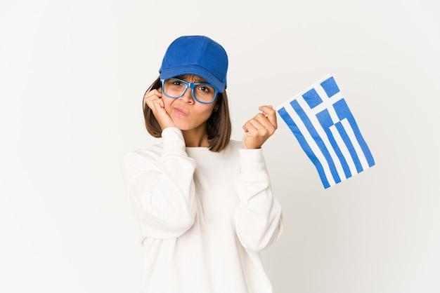 손으로 귀를 덮고 그리스 국기를 들고 젊은 히스패닉 혼혈 여자.
