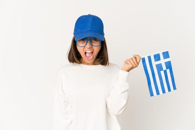 非常に怒って攻撃的に叫んでギリシャの旗を持っている若いヒスパニック混血の女性。
