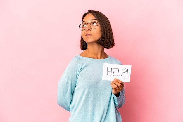 목표와 목적 달성을 꿈꾸는 도움말 포스터를 들고 젊은 히스패닉 혼혈 여자