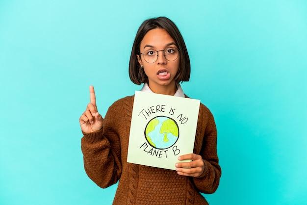 Молодая латиноамериканская женщина смешанной расы, держащая плакат сохранения планеты, имеющая отличную идею, концепцию творчества.