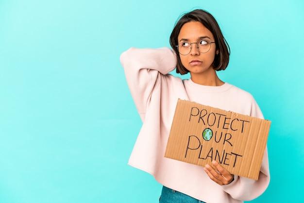 Молодая испанская женщина смешанной расы, держащая картон защиты нашей планеты, касаясь затылка, думая и делая выбор.