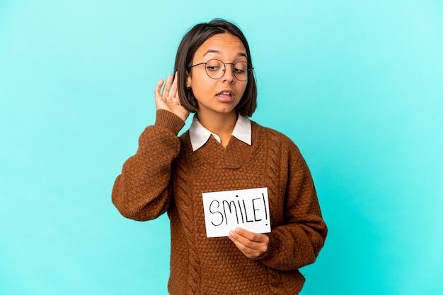 Молодая латиноамериканская женщина смешанной расы, держащая примечание улыбки, пытаясь выслушать сплетню.