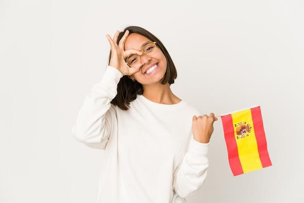 Молодая латиноамериканская женщина смешанной расы, держащая испанский флаг, взволнована, держа на глазах хорошо жест.