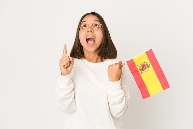 열린 된 입으로 거꾸로 가리키는 스페인 국기를 들고 젊은 히스패닉 혼혈 여자.