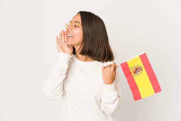 Молодая латиноамериканская женщина смешанной расы, держащая испанский флаг, кричит и держит ладонь возле открытого рта.