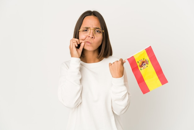 비밀을 유지하는 입술에 손가락으로 스페인 국기를 들고 젊은 히스패닉 혼혈 여자.