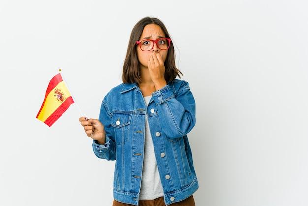 Молодая латиноамериканская женщина смешанной расы держит испанский флаг